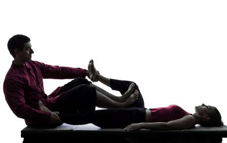 one man and woman perfoming feet legs thai massage in silhouette studio on white background Stock Photo - 15800570
