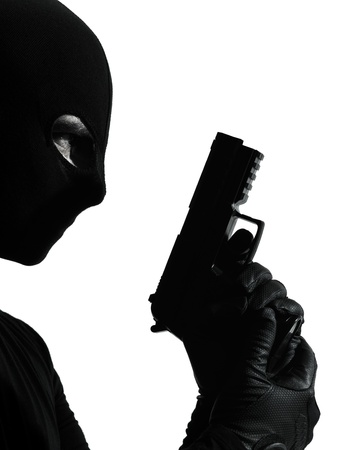 intruder: thief criminal terrorist holding gun portrait in silhouette studio isolated on white background Stock Photo