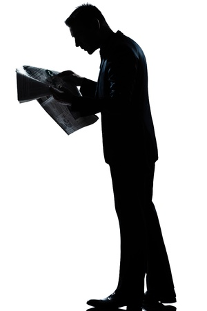 man side view: one caucasian man walking reading newspaper  full length silhouette in studio isolated white background