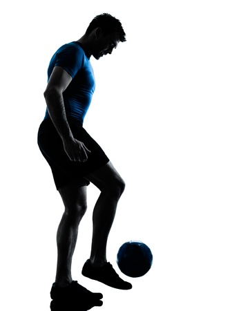 one caucasian man playing soccer juggling football player silhouette  in studio isolated on white background photo