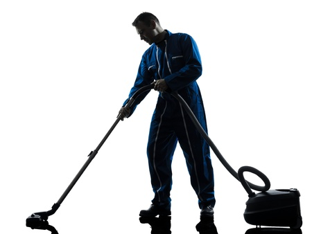 cleaning service: one caucasian janitor vaccum cleaner cleaning silhouette in studio on white background