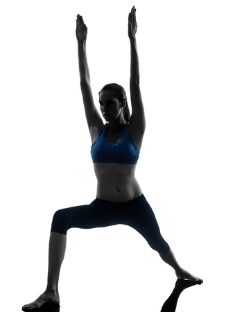 crouches: one caucasian woman exercising yoga in silhouette studio isolated on white background