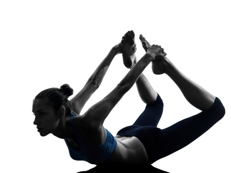 exercise silhouette: one caucasian woman exercising yoga  bow pose in silhouette studio isolated on white background Stock Photo