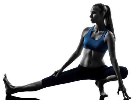 warm up: una donna indoeuropea esercita gambe yoga si estende scaldare in studio, silhouette, isolato su sfondo bianco