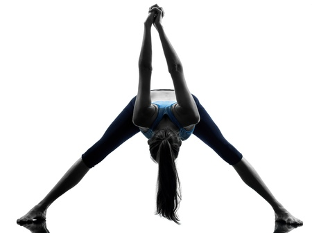woman posture: one caucasian woman exercising yoga stretching legs warm up in silhouette studio isolated on white background