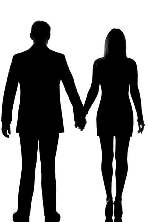 person silhouette: one lovers caucasian couple man and woman standing hand in hand in studio silhouette isolated on white background