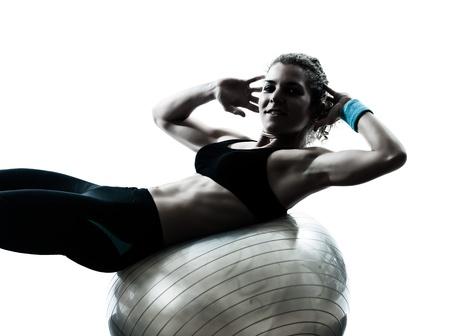 gimnasia aerobica: una mujer caucásica ejercicio físico postura entrenamiento pelota en el estudio de la silueta aislado en el fondo blanco