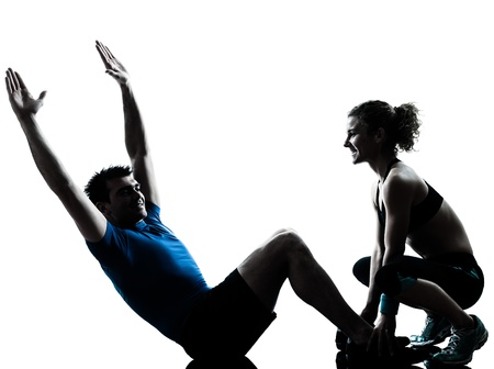 indoor shot: one caucasian couple man woman personal trainer coach exercising abdominal silhouette studio isolated on white background