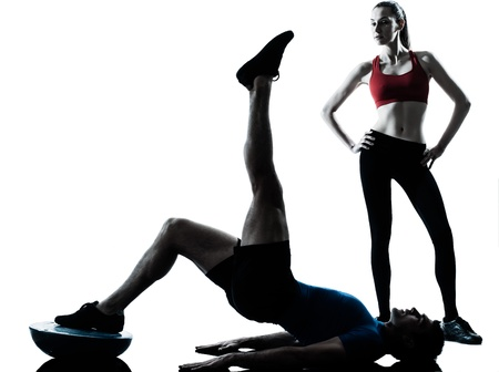push ups: personal trainer man coach and woman exercising abdominals push ups on bosu silhouette  studio isolated on white background