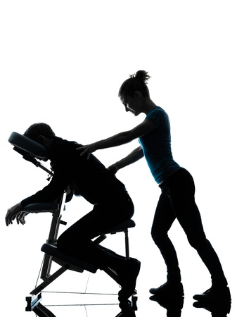 masajes relajacion: un hombre y una mujer perfoming masaje silla en el estudio de la silueta en el fondo blanco