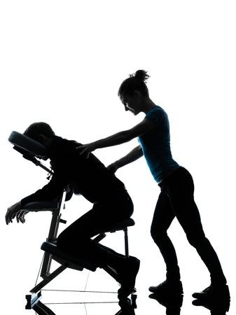 massaggio: un uomo e una donna perfoming massaggio alla schiena sedia in studio silhouette su sfondo bianco
