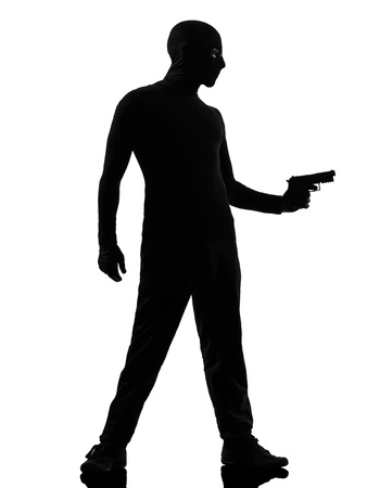 man holding gun: thief criminal terrorist man aiming gun in silhouette studio isolated on white background