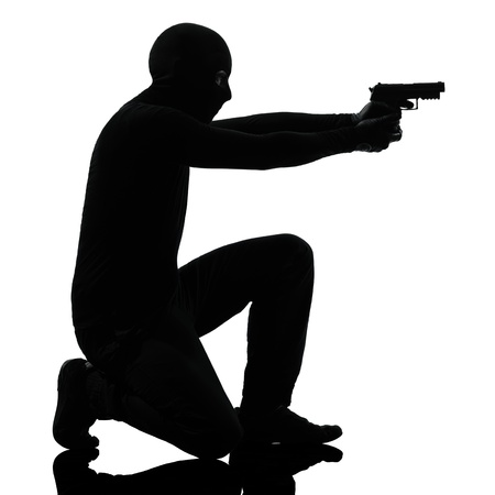 thief criminal terrorist man aiming gun in silhouette studio isolated on white background Stock Photo - 15894781