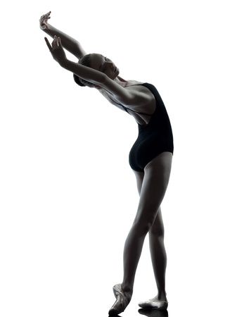 ballet: one caucasian young woman ballerina ballet dancer stretching warming up in silhouette studio on white background Stock Photo