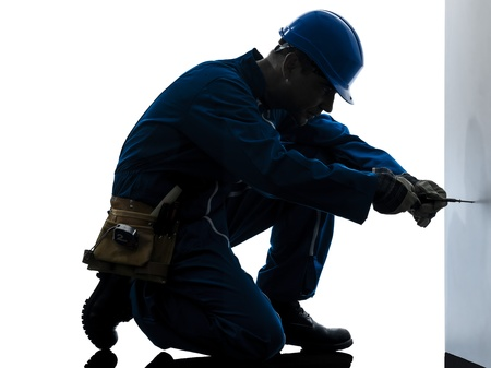 foremen: one caucasian man construction worker screwdriving silhouette in studio on white background