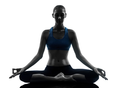 meditating woman: one caucasian woman exercising yoga meditating in silhouette studio isolated on white background Stock Photo