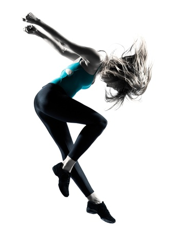 Side view of blond haired woman doing gymnastic jump in studio on white background photo