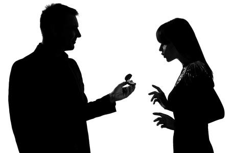 siluetas de enamorados: un hombre cauc�sico par que ofrece el anillo de compromiso y una mujer sorprendida en estudio, silueta, aislado sobre fondo blanco
