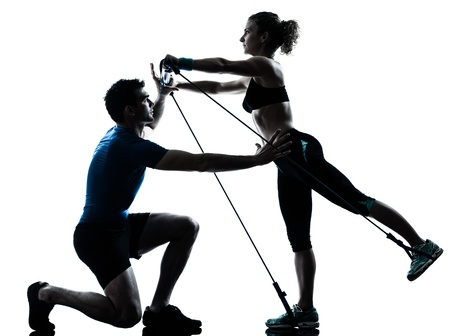 trainer: one caucasian couple man woman personal trainer coach exercising gymstick silhouette studio isolated on white background Stock Photo
