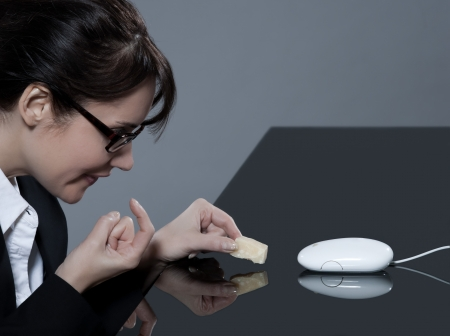 secretary desk: beautiful brunette business woman at her desk trying to trap her computer mouse with cheese