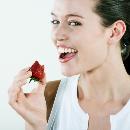 studio portrait on isolated background of a young beautiful caucasian woman eating a strawberry photo
