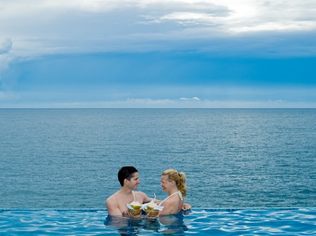 honeymooners: beautiful caucasian couple enjoying their vacation in a swimming pool by the seaside drinking coconut milk Stock Photo