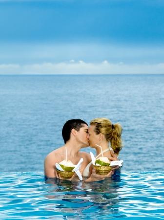 honeymooners: beautiful caucasian couple enjoying their vacation in a beautiful swimming pool by the seaside