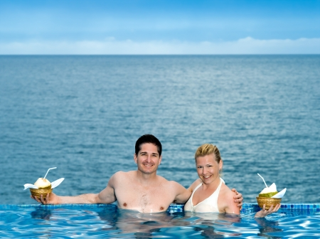 coconut drink: beautiful caucasian couple enjoying their vacation in a beautiful swimming pool by the seaside