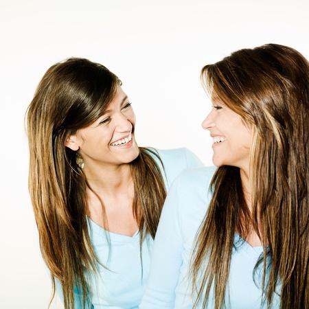 gemelas: foto de estudio retrato sobre fondo aislado de dos hermanas gemelas amigas
