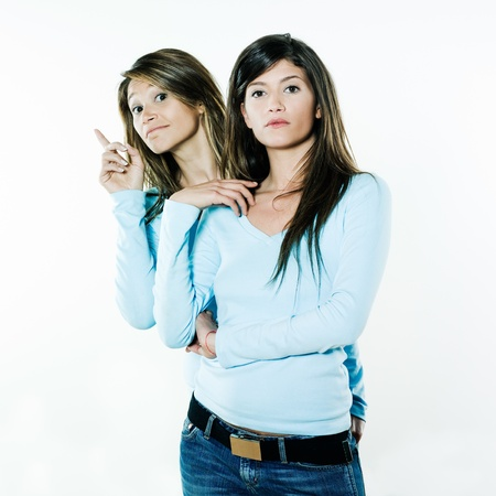 studio shot portrait on isolated background of two sisters twin women friends one raising from the back of the other photo