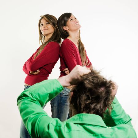 studio shot pictures on isolated background of two sisters twin women friends in front of a man tearing his hair away photo