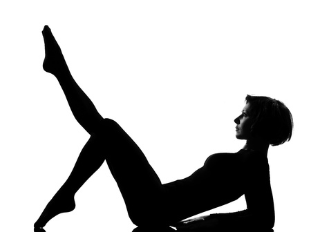 woman exercising lying on back fitness yoga stretching in shadow grayscale silhouette full length in studio isolated white background photo