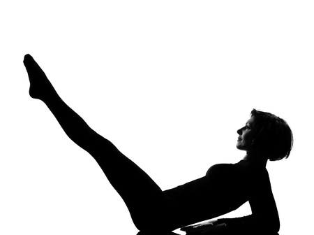 lying on back: woman paripurna navasana boat pose yoga exercising lying on back fitness yoga stretching in shadow grayscale silhouette full length in studio isolated white background