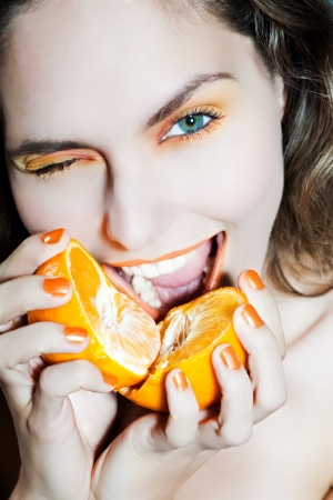 studio portrait of a beautiful woman holding orange mandarine citrus fruit photo