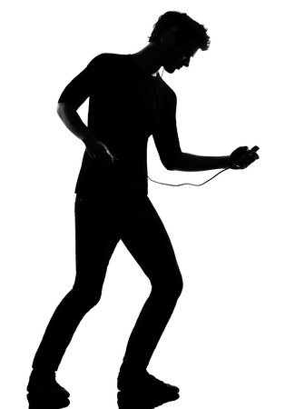 air guitar: young man listening music audio player silhouette in studio isolated on white background