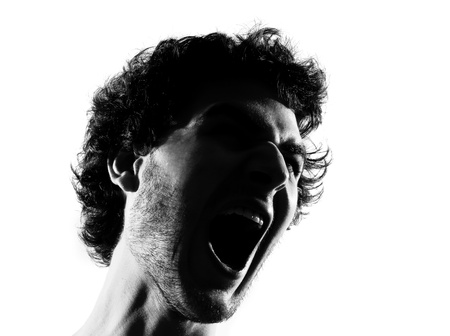 man face close up: young man screaming angry portrait silhouette in studio isolated on white background Stock Photo