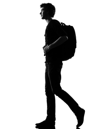 young man backpacker walking silhouette in studio isolated on white background photo