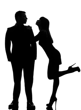 adult profile: one caucasian couple lovers  woman wanting to kiss the man in studio silhouette isolated on white background