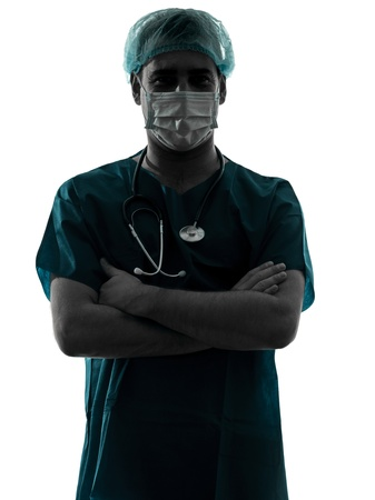 cirujano: un m�dico cauc�sico cirujano Retrato de hombre con los brazos mascarilla trabajadores m�dicos silueta cruz� aislado sobre fondo blanco Foto de archivo