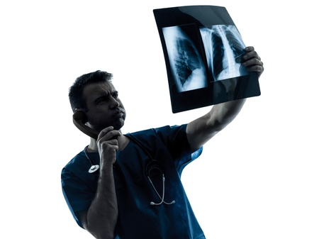 one caucasian man doctor surgeon radiologist medical examaning lung torso  x-ray image silhouette isolated on white background Stock Photo - 16410142