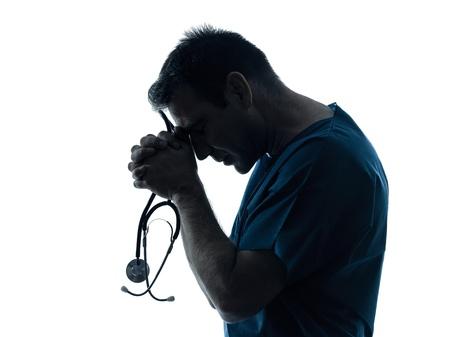 desperate: un hombre caucásico médico cirujano silueta trabajador médico rezando aisladas sobre fondo blanco Foto de archivo