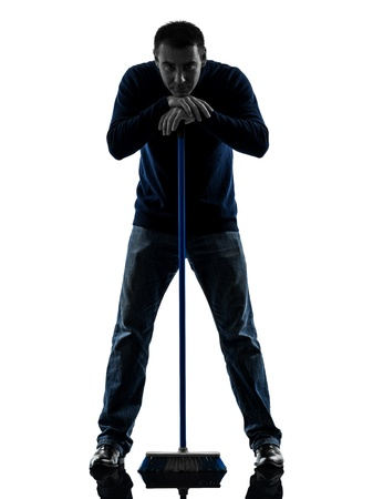 brooming: one causasian man janitor brooming cleaner boredom full length in silhouette studio isolated on white background Stock Photo