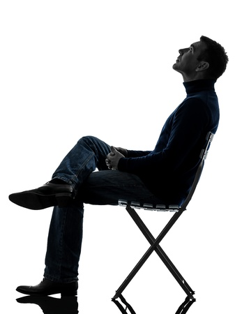 one causasian man sitting looking up   full length in silhouette studio isolated on white background photo