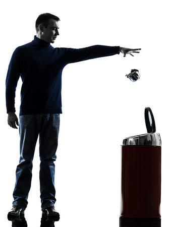 dropped: un hombre causasian dejar caer un papel en una longitud de basura lleno en el estudio de la silueta aislado en el fondo blanco