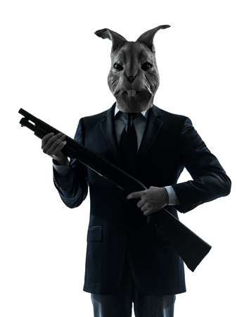 animal masks: one causasian man rabbit mask hunting with shotgun portrait in silhouette studio isolated on white background