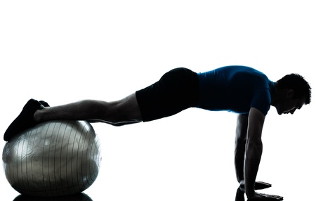 plank position: one caucasian man exercising workout fitness ball in silhouette studio  isolated on white background