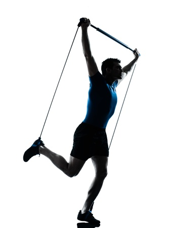 pilates man: one caucasian man exercising gymstick workout fitness in silhouette studio  isolated on white background