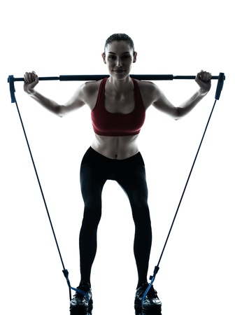 crouches: one caucasian woman exercising elastic gymstick in silhouette studio isolated on white background