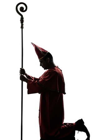 kneel down: one man cardinal bishop silhouette in studio isolated on white background