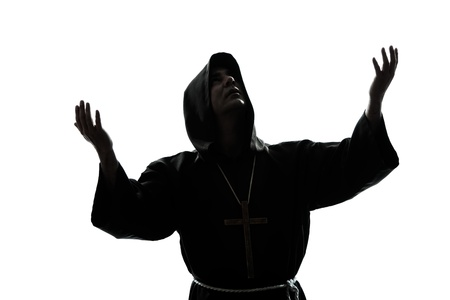 arms  outstretched: one caucasian man priest praying silhouette in studio isolated on white background Stock Photo